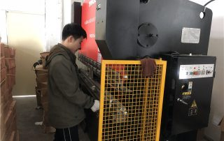 Workers work on Press Bracket Machine for TV bracket