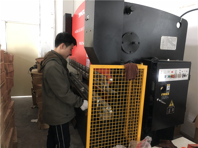 Workers work on Press Bracket Machine for TV bracket