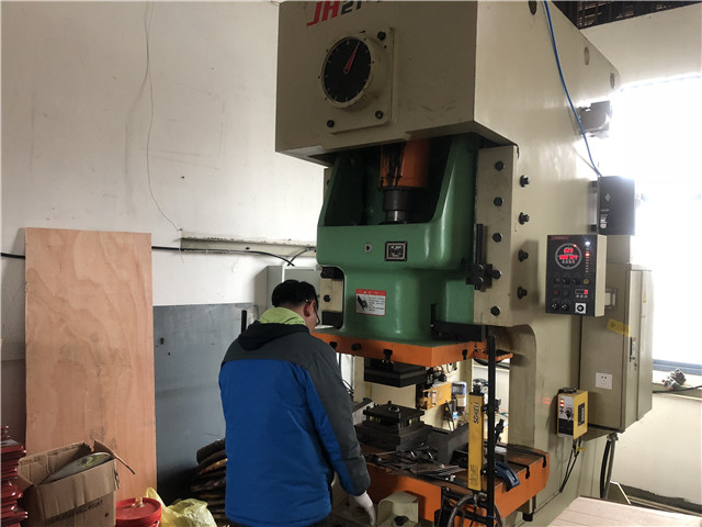 Workers work on punching machine for TV bracket
