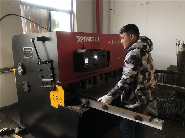Workers work on shearing machine for TV bracket